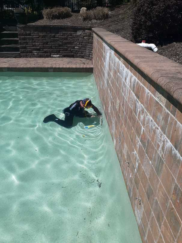 Rin Robyn Pools service technician shown with diving gear checking for leaks in a pool.