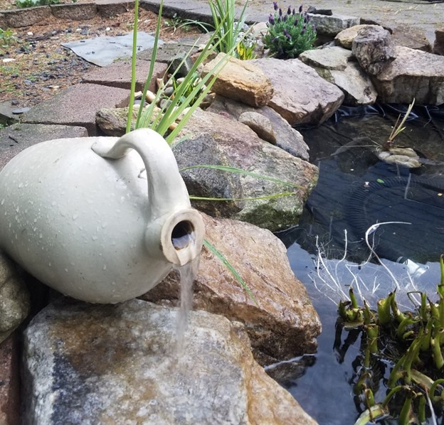 Example of a pond install shows a water feature an overturned jug fountain.